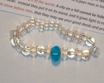 CONFORMITY BRACELET, DO NOT CONFORM TO THIS WORLD, bracelet, off white beads with one turquoise or blue color bead, be different
