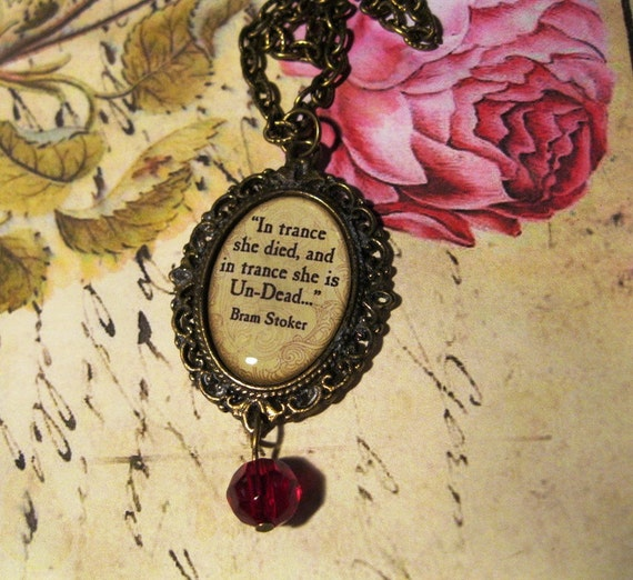 """Bram Stoker Quote Necklace - """"In trance she is Un-Dead"""",  In oval bronze setting beneath resin, blood red accent bead"""