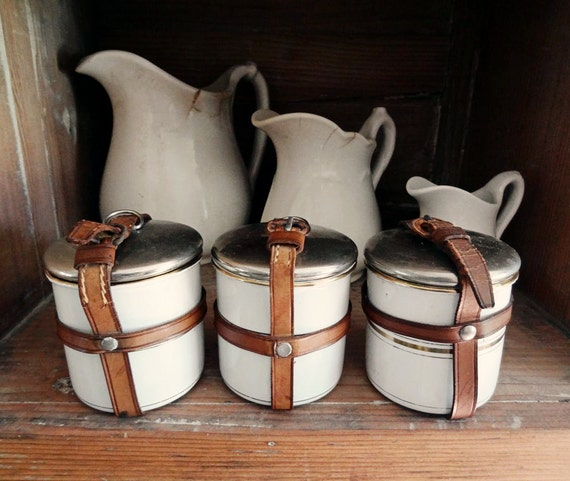 vintage enamelware canisters, 3 small tins with leather straps, white with gold striping from Germany