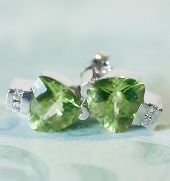 Magnificent pair of trillion peridot 14k white gold and diamond earrings.