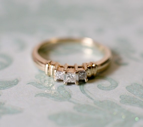 Attractive three stone princess cut engagement ring in 14k yellow gold.