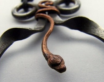 pendant, a snake inside a forged iron frame