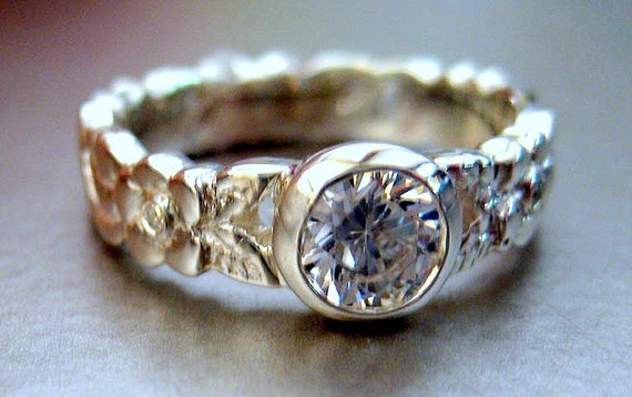 Engagement ring.  White sapphire in the center.  Leaf design