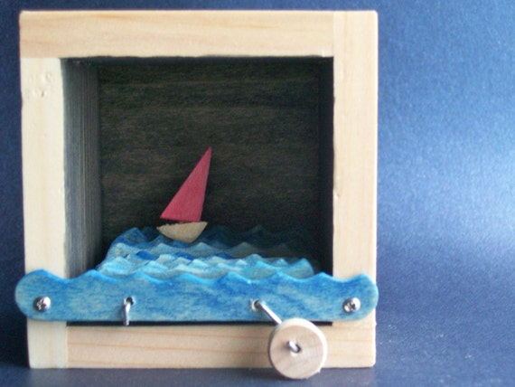 red sailboat in black box automata