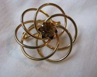 Gold tone circular brooch pin with amber topaz rhinestone
