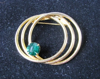 Triple gold tone circle vintage brooch pin with  Kelly green rhinestone.