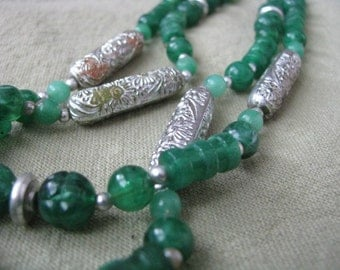 Vintage beaded necklace in shades of green with silver tone floral beads