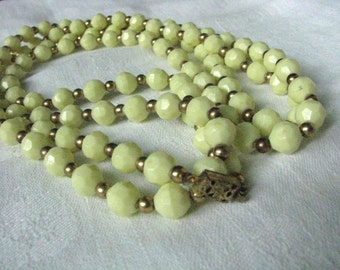 Long pale yellow vintage beaded necklace with gold tone spacers