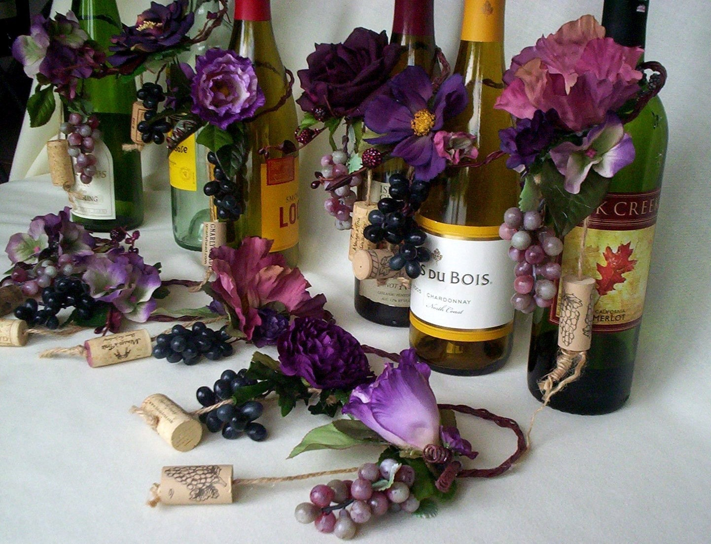 Plum wedding centerpiece wine bottle toppers grapes custom for Wedding table decorations with wine bottles