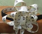Tape Measure Headband with White Rosette Flower Adornment on Black Satin Headband