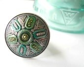 Large green ring with blue and silver detail. Adjustable antiqued brass ring with metallic silver cabochon.