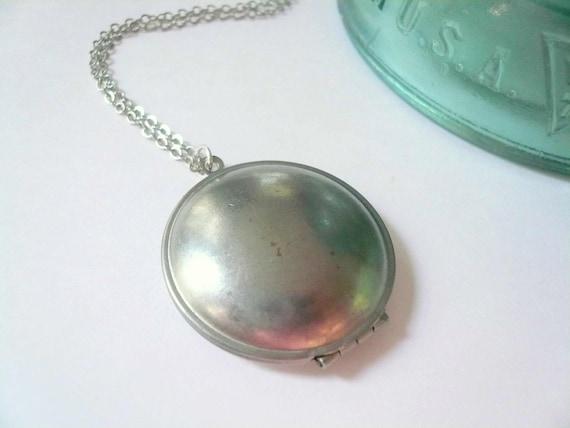 Silver locket necklace. Subtle grey rusting steel.