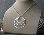 Large pendant necklace. Sterling silver ascending circle halo design. Trio of rings pendant on long or short chain. Boho chic gift for women