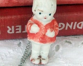 A Chippy little Porcelain Doll in a Red Dress Necklace
