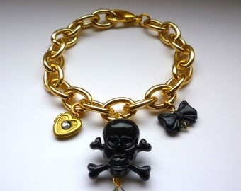 Gold tone charm bracelet with lucite skull, bow and locket
