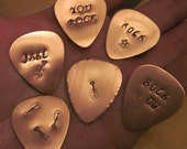 Copper Guitar picks you choose what it says