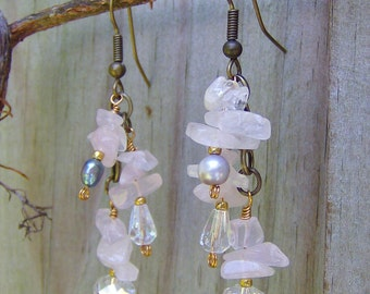 Fresh water pearls in lavender and gray hues drop from rose quartz flower gemstones reminding me of graceful wisteria vines in bloom...