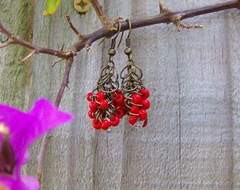 Antique gold metal is hand fabricated in a lush cluster of elegant beauty, embellished with plump lipstick red beads and Swarovski crystals