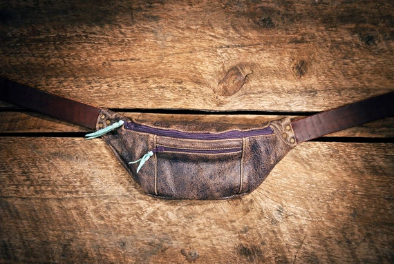 Distressed purple handcrafted leather (cowhide) fanny pack - hand cut, sewn, and riveted - Electric purple zips, teal pull tabs.