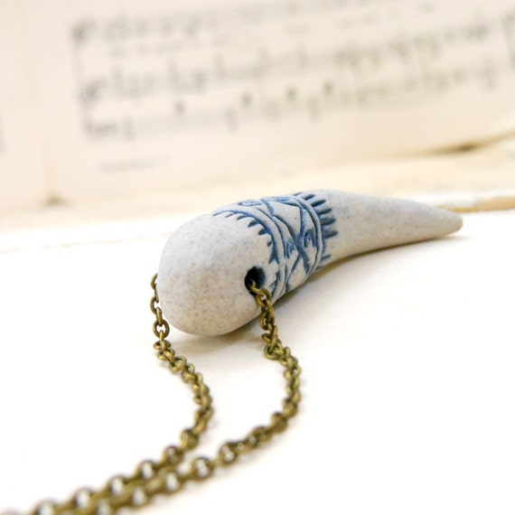 Tribal tusk or tooth with blue geometric pattern diamonds circles