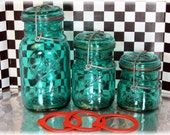 Bevy of Ball Bail Bottles Jars in Green With Centennial Markings on Back