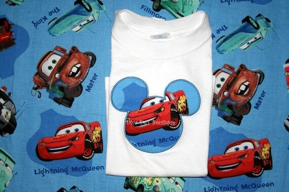MM head filled with race car material appliqued on  short sleeved t shirt children and adult sizes
