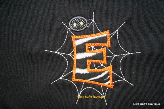Spider on initial in a web appliqued on a black short sleeved tee shirt children and adult sizes