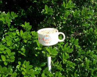Teacup birdfeeder poke creates a charming addition to your flower garden