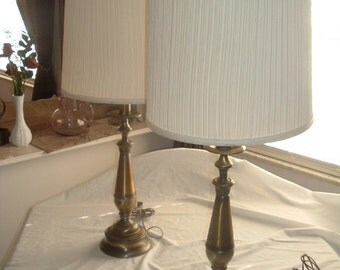 a pair of vintage brass candle stick lamps