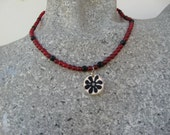 Red and black beaded necklace with Shrinky Dink flower pendant