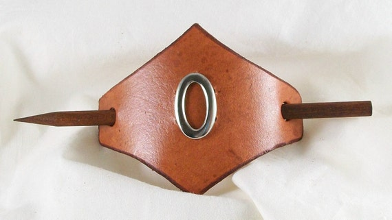 Leather hair barrette with a simple ornament in the center