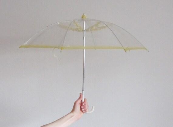 r e s e r v e d clear plastic bubble umbrella . 1950 parasol . yellow trim and flowers .sale