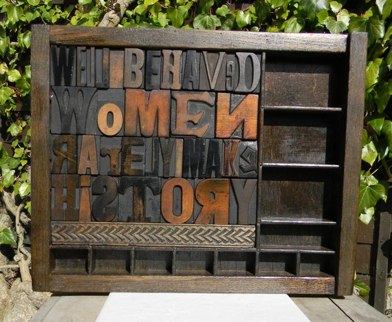 Well behaved women rarely make history,  a collage of vintage wooden print blocks set in a type tray / case