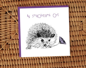 Ag Smaoineamh Ort, 'Thinking of You'.  Hedgehog with purple daisy ink Illustrated card