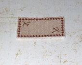 handstitched dollhouse rug in cream and red