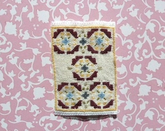 dollhouse carpet, handstitched in red, blue, and yellow