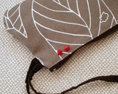 Grey wristlet with white leaves and contrasting white and red lining