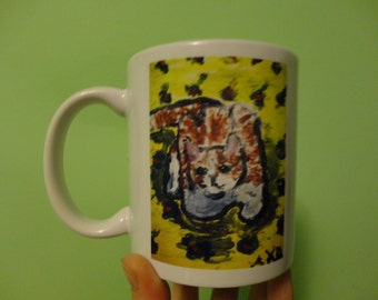 Ceramic Mug, 5 inches high.  Picture of cute marmalade cat on bright yellow bedspread