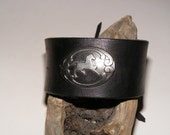 Leather wrist band with a metal concho.