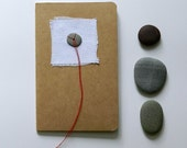 blank moleskine notebook red thread white black pebble