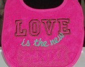 Hot pink Embroidered baby bib with saying Love is the new pink