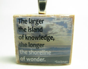 The larger the island of knowledge - Scrabble tile with Sockman quote on beach background