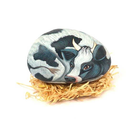 Painted rock, black and white cow