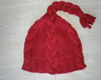 Hand-knitted dark red hat with cables and tassle
