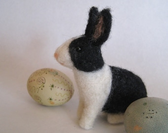 A bunny in black and white, needle felted animal sculpture