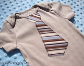 Brown, Blue, and tan striped necktie on a beige bodysuit