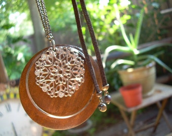 OOAK Necklace featuring a suede type leather with a circular wooden disc and a openwork metal filigree style disc