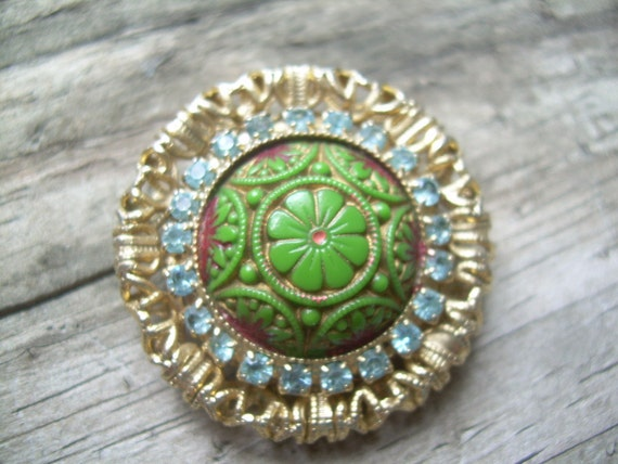 stunning Vintage brooch, Gold filigree with Blue rhinestones surrounding a plastic carved cabochon with green enamel