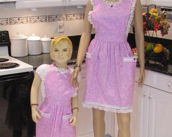 MOTHER  DAUGHTER  APRON set in a mauve, lavender print, retro style with shawl collor,two pockets,embroided ribbon and lace