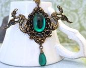 VINTAGE EMERALD, antique brass twin dragon necklace with green vintage Swarovski glass cab